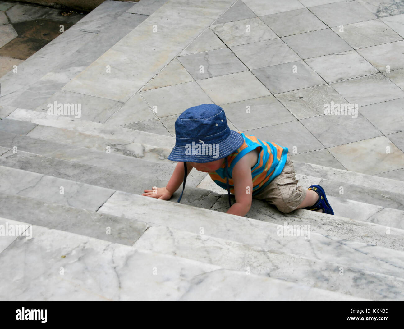 A little baby clambering up the big marble stairs - Stock Image