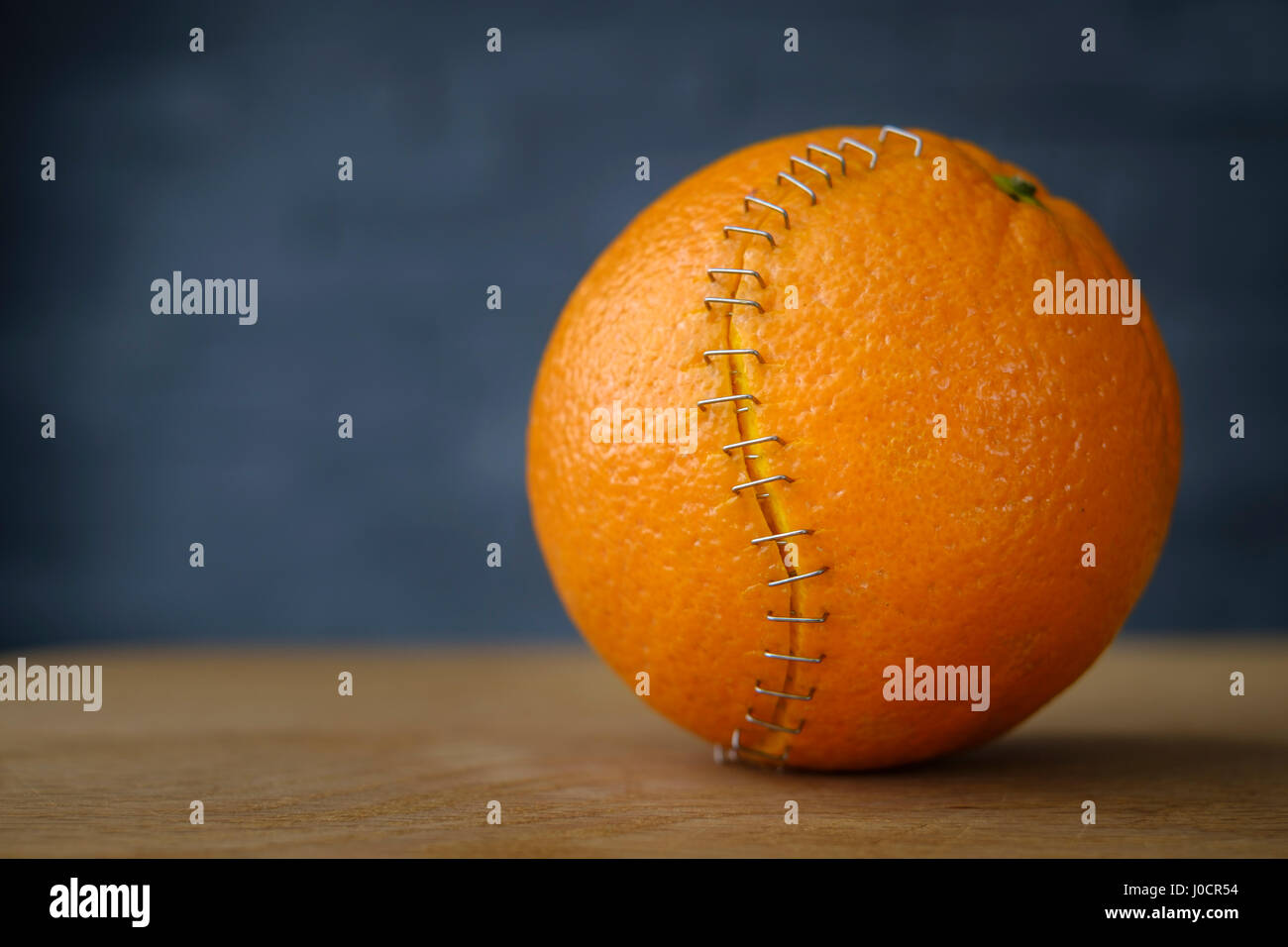 orange with stainless steel stitches that hold the husk together - Stock Image