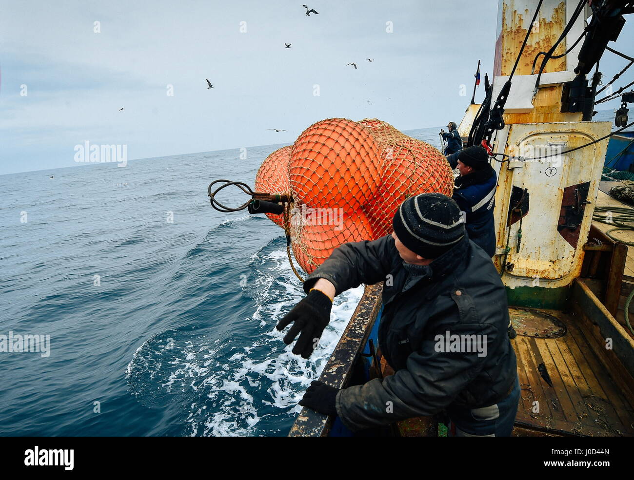 Primorye Territory, Russia. 11th Apr, 2017. A fisher throws a buoy from an MRS-450 commercial fishing boat of the - Stock Image