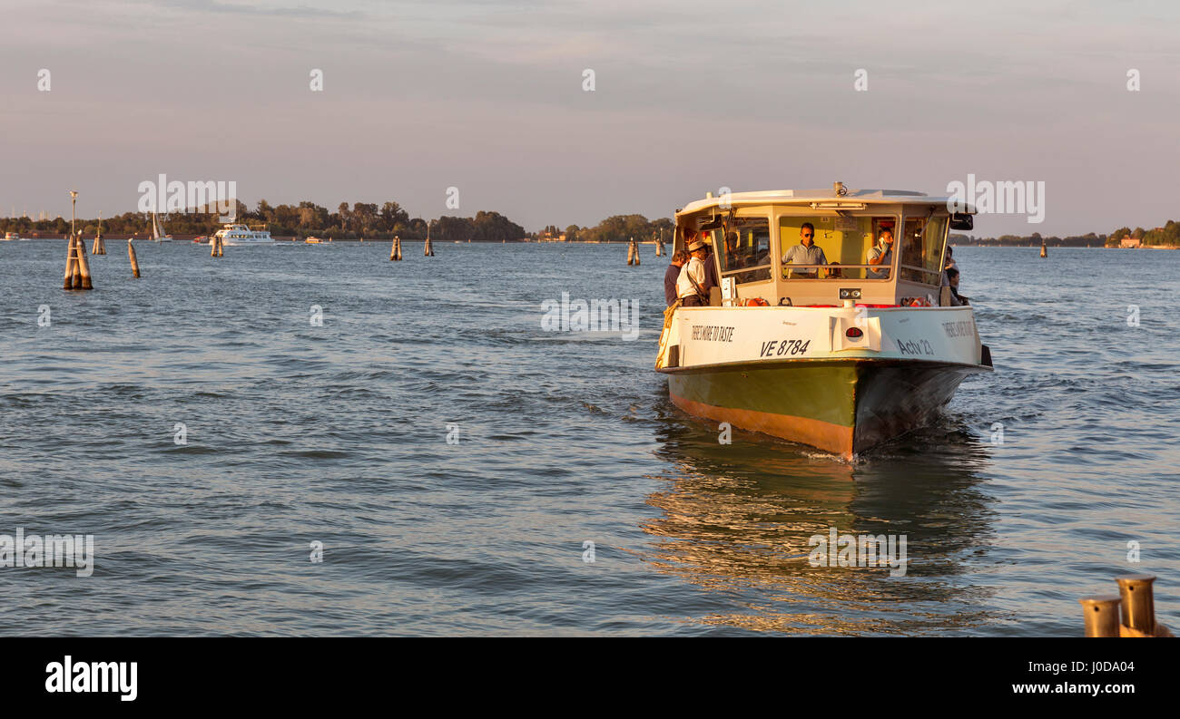 VENICE, ITALY - SEPTEMBER 23, 2016: Vaporetto with passengers sails in Venice lagoon at sunset. Venice is situated - Stock Image