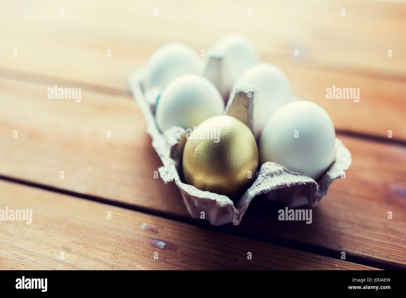 close up of white and gold eggs in egg box Stock Photo