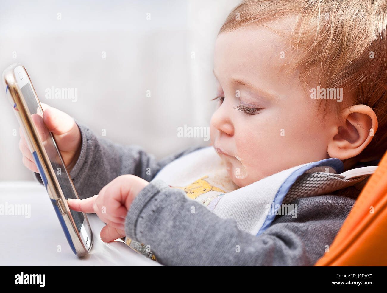 little kid try to use modern smartphone during dinner - Stock Image