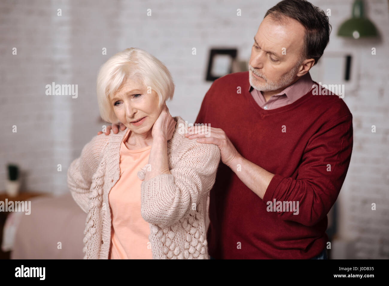 Feeling spasm. Pretty elderly woman standing and touching her aching neck while her husband supporting her. - Stock Image