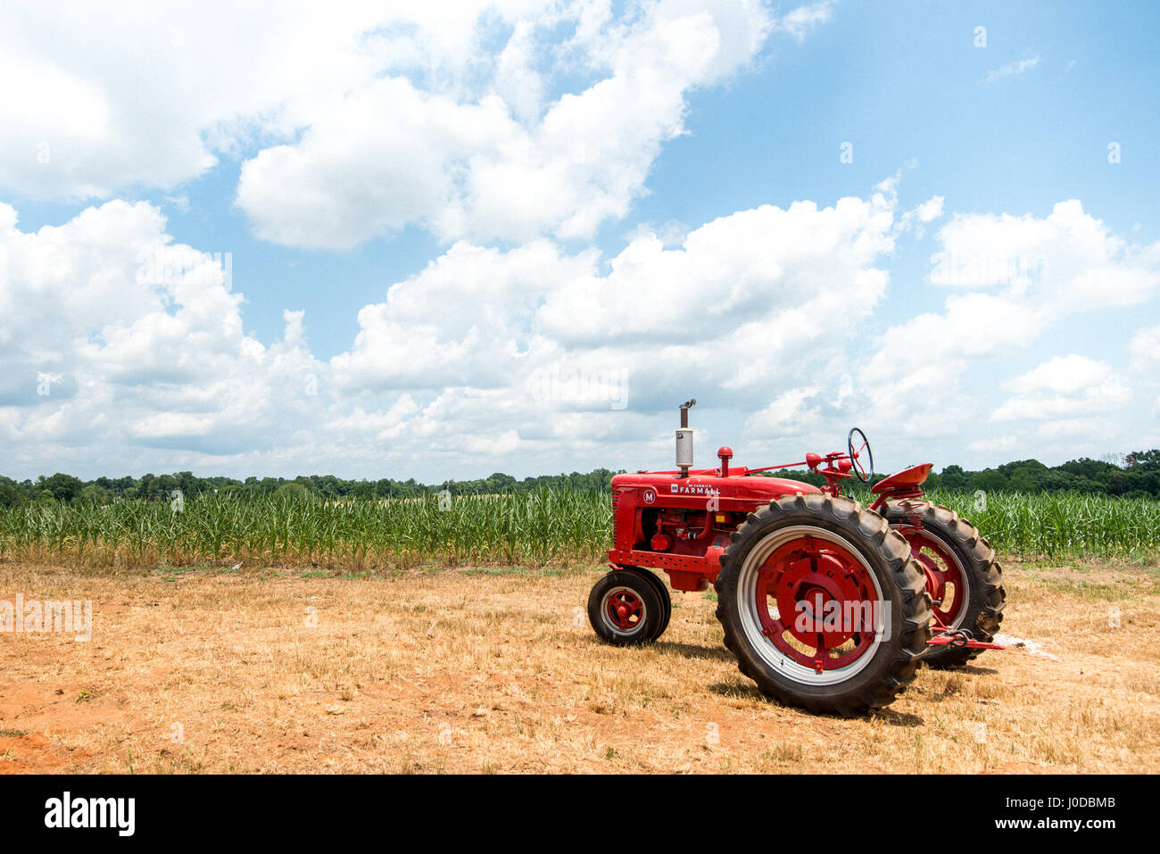 A red McCormick Farmhall tractor in front of a field in North Carolina during the summer months. Stock Photo