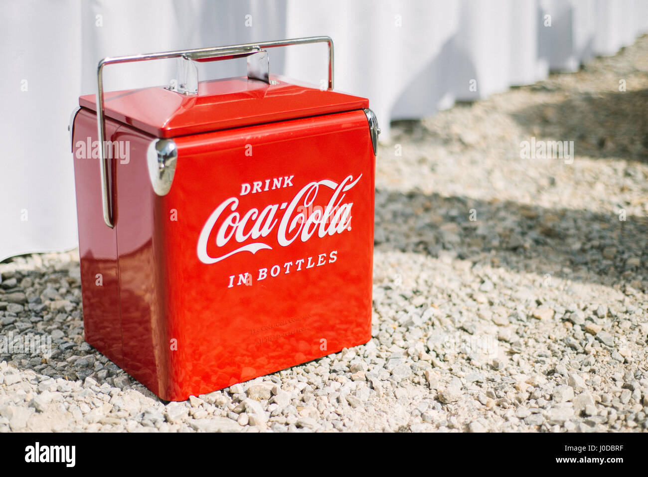 Red vintage Coca-Cola cooler in sunshine. Stock Photo