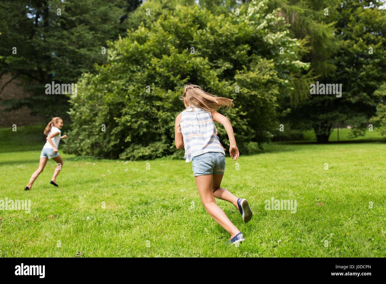 happy kids or friends playing outdoors - Stock Image