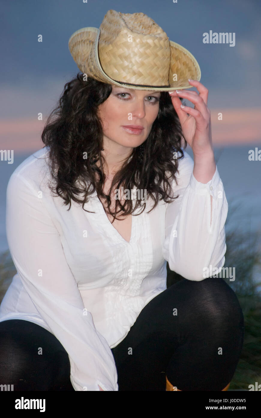 1308ce42e7c11 Beautiful brunette girl by the sea wearing a cowboy hat Stock Photo ...