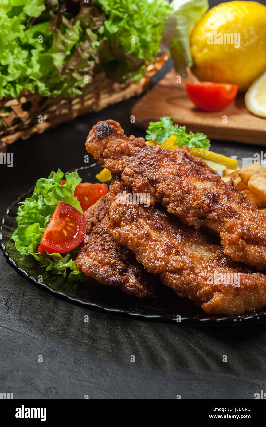 Fried fish in crispy batter with chips on a plate - Stock Image