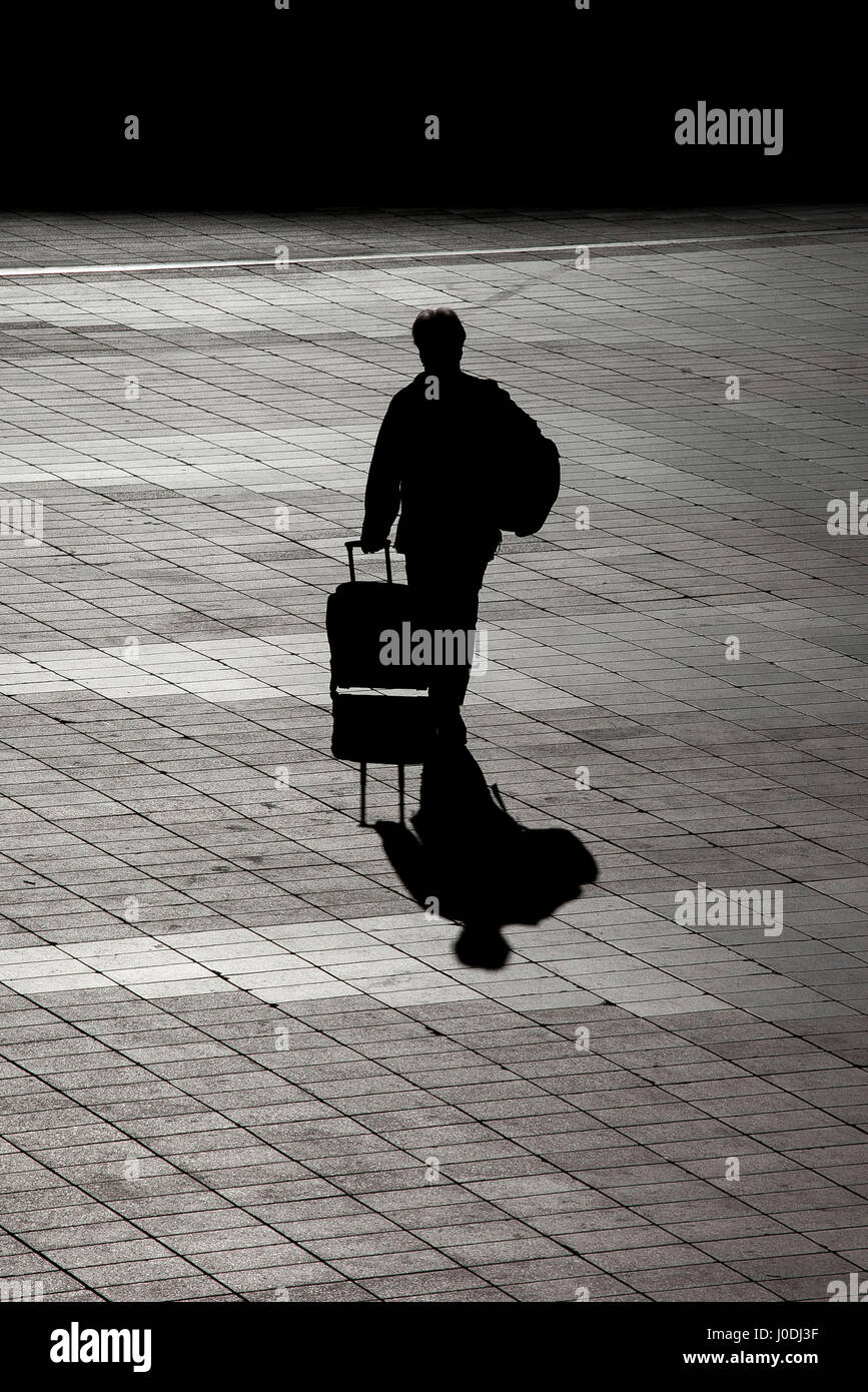 silhouette of a traveler with a suitcase coming back home stock