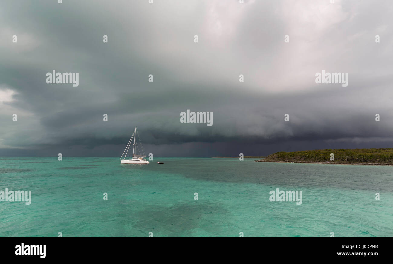 A dark squall storm cloud over the calm green water of a Bahama bay as a catamaran sailboat lies in a calm anchorage. - Stock Image