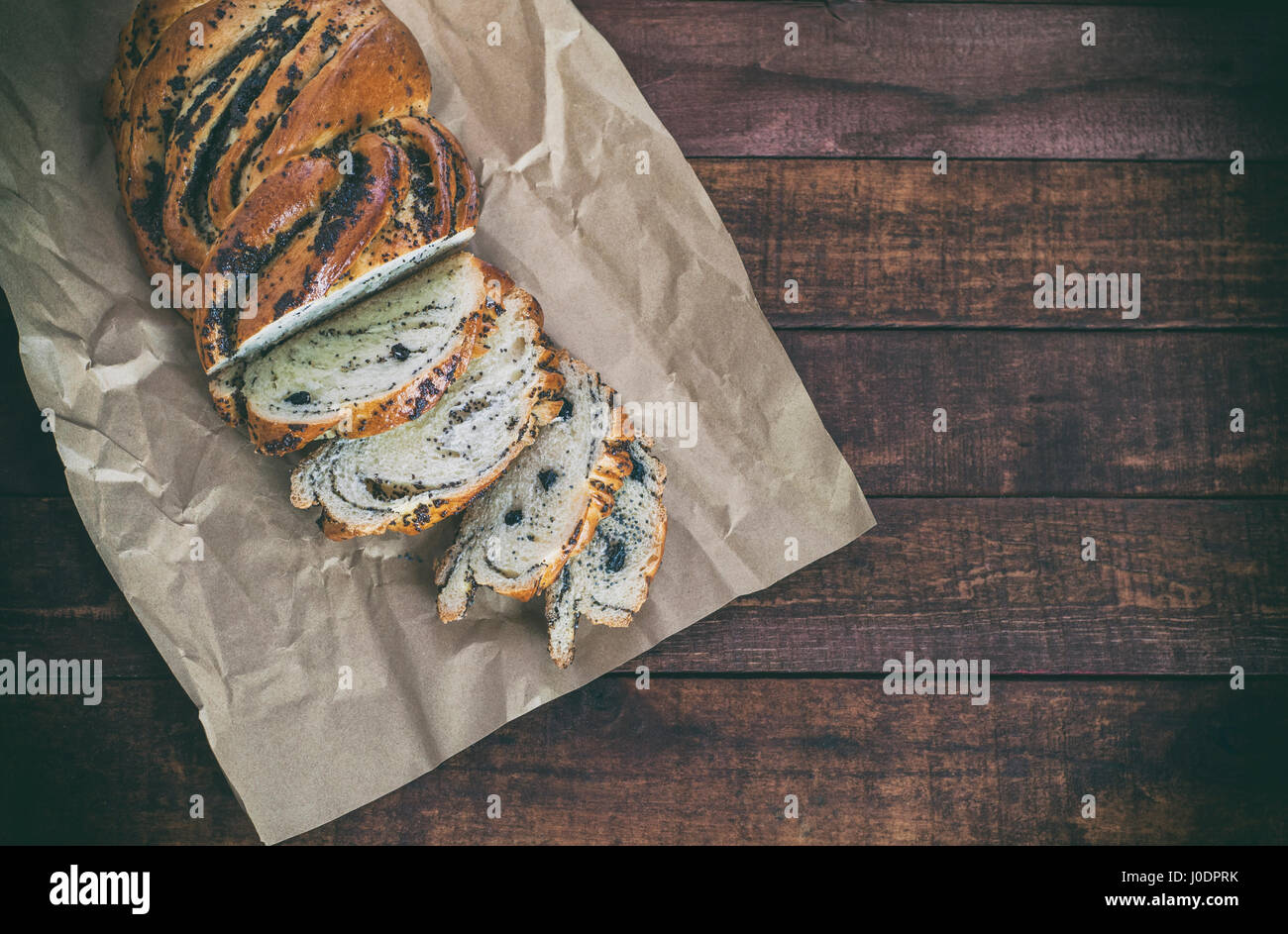 Bun with poppy seeds on kraft paper, empty space on the right, vintage toning - Stock Image