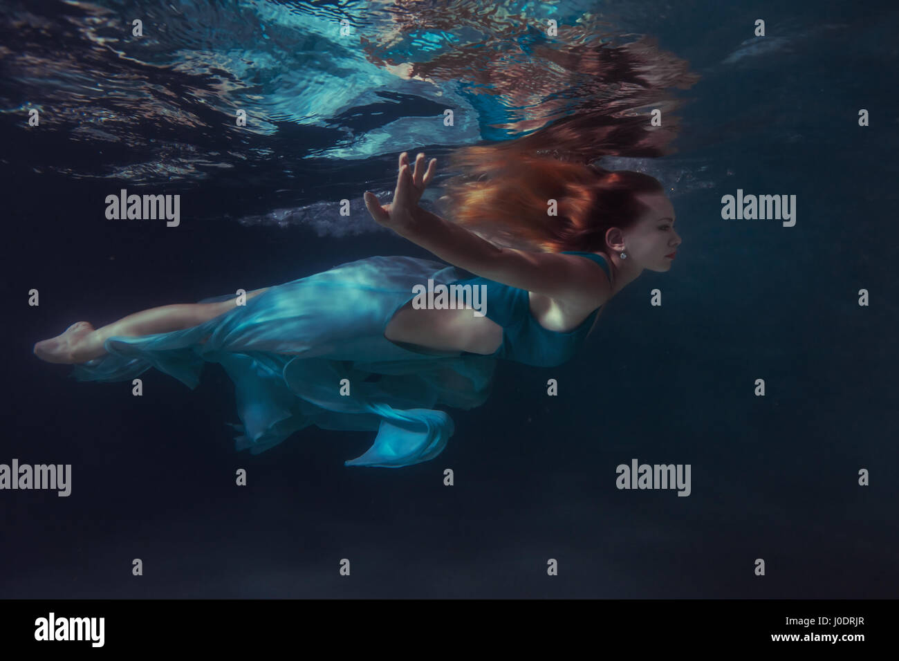 Woman in a dress swims under water, her hair develop in water. - Stock Image