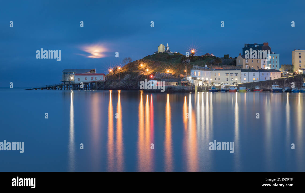 The 'pink' April full moon rises over a serene Tenby Harbour at high tide. Pembrokeshire in Wales - Stock Image