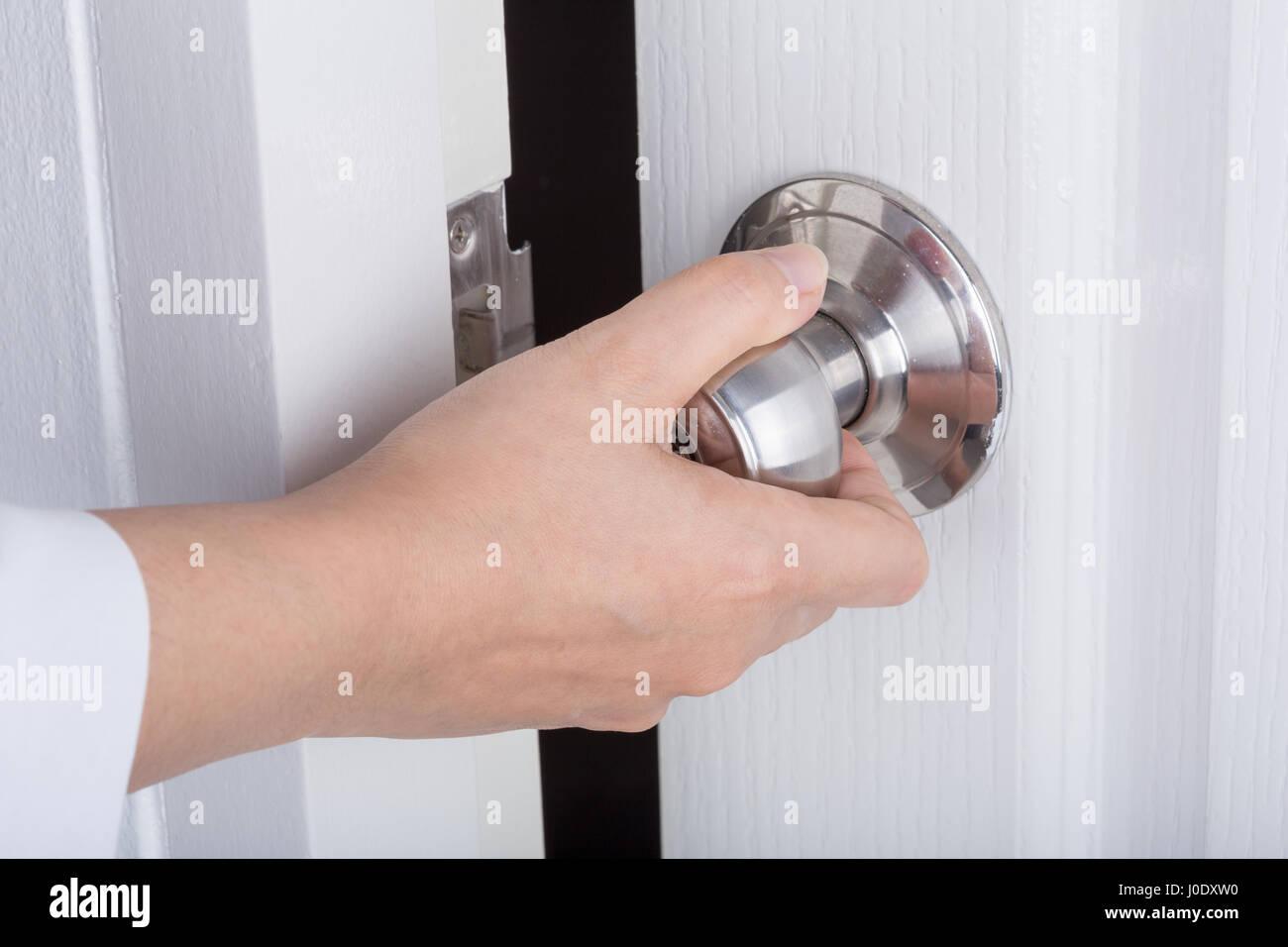 Hand opening door knob on the white door Stock Photo: 137989404 - Alamy