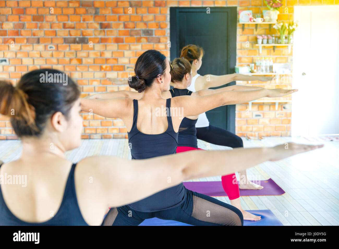 Fitness asian female group doing warm up yoga pose in row at the yoga class. selective focus - Stock Image