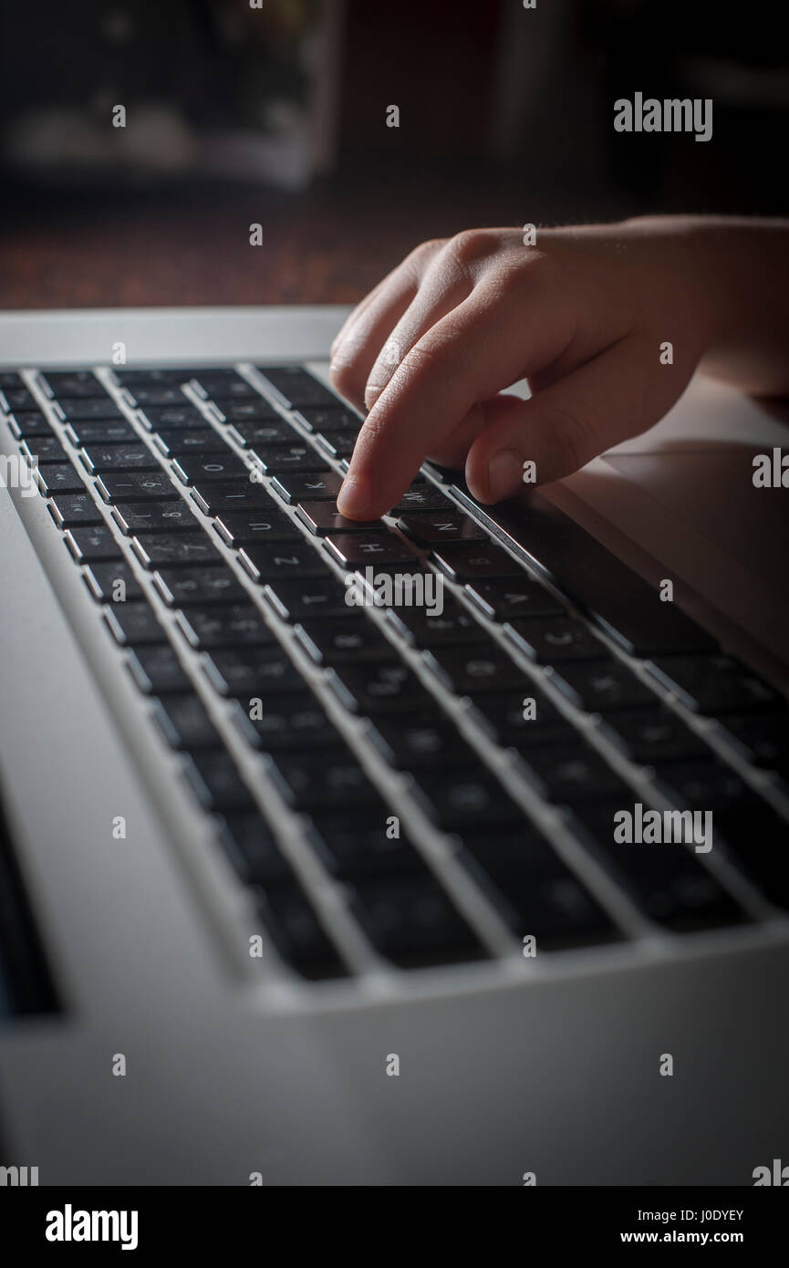 Young girl using a laptop computer. - Stock Image