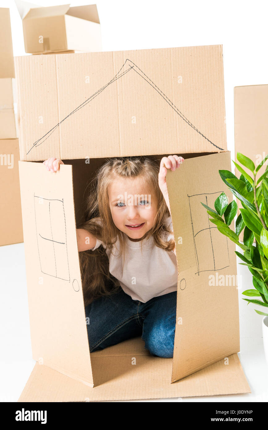Cute little girl sittling inside of cardboard box with house drawed on it - Stock Image