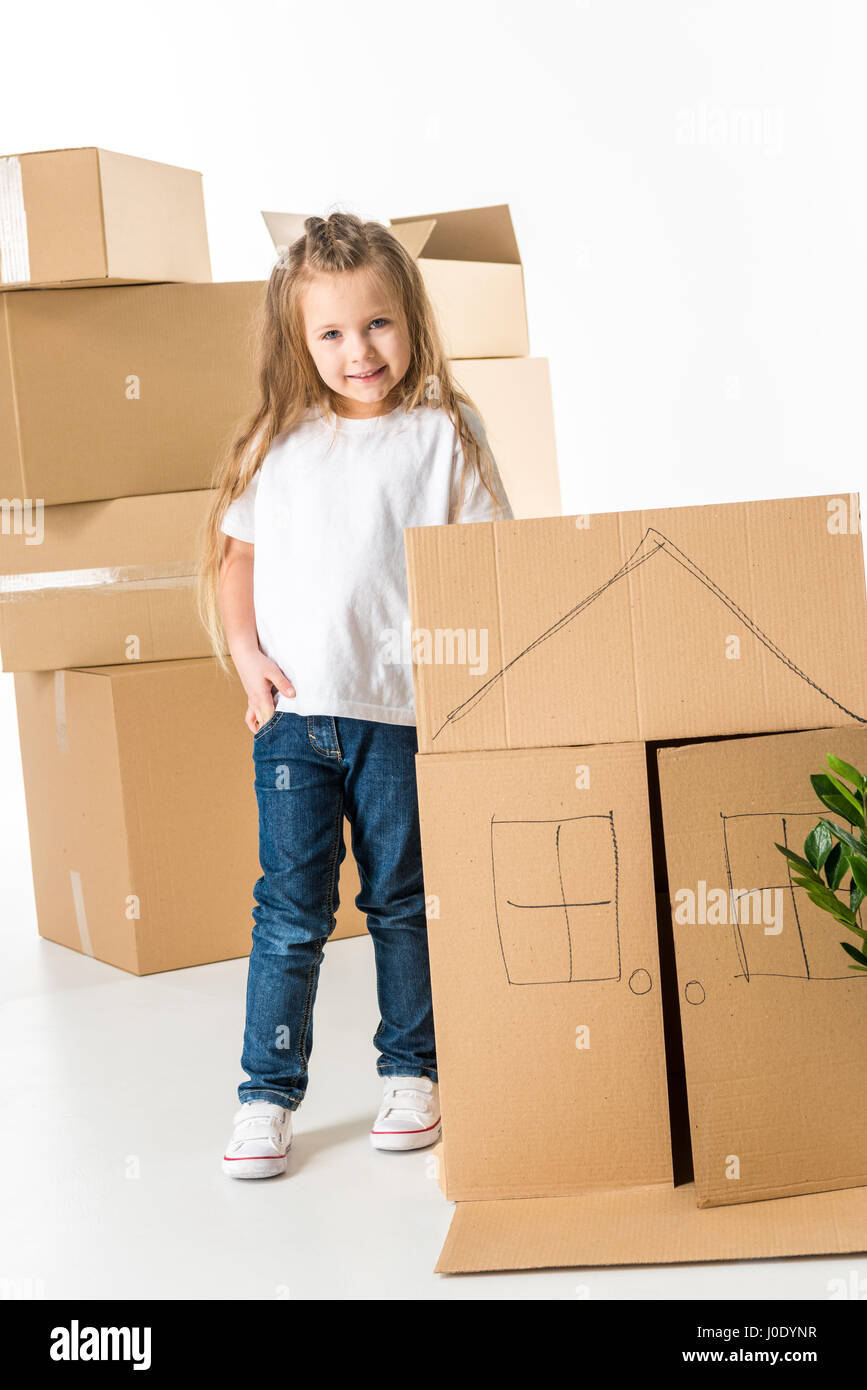 Little girl standing near cardboard box with house drawed on it - Stock Image
