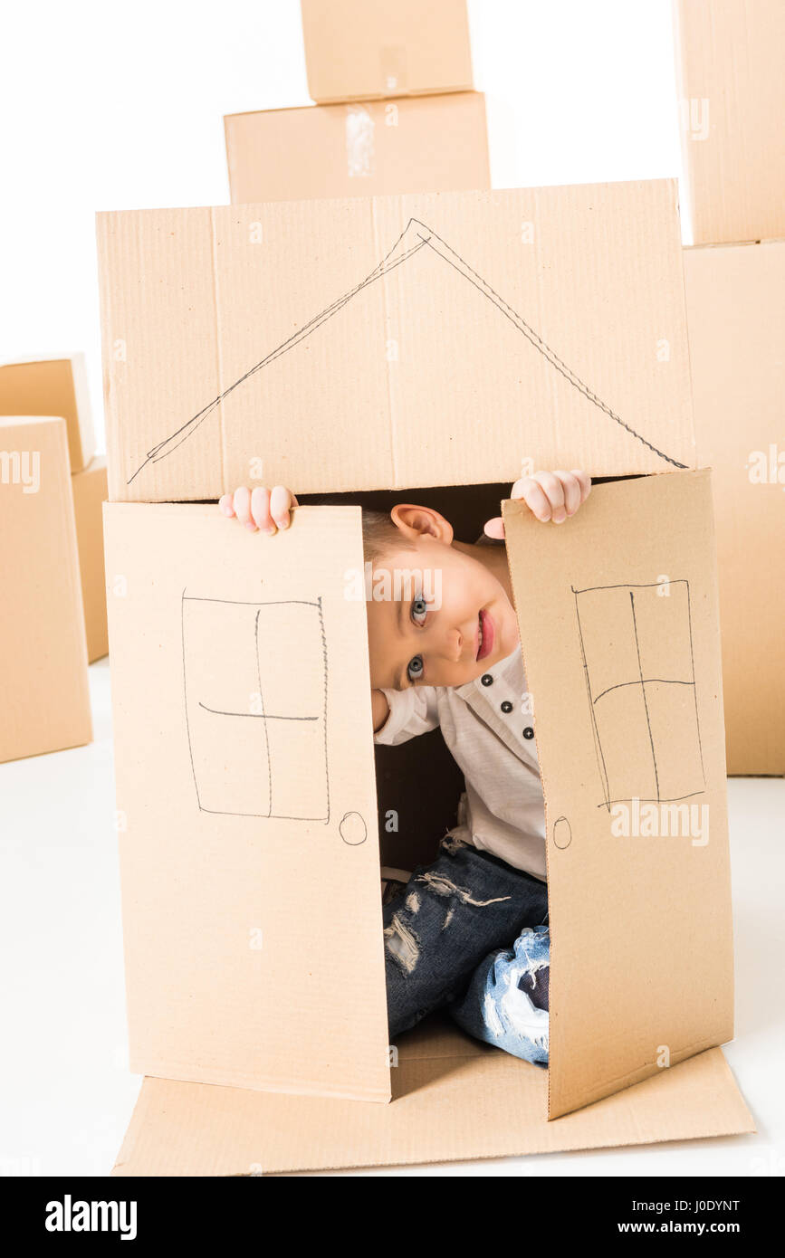 Cute little boy sittling inside of cardboard box with house drawed on it - Stock Image