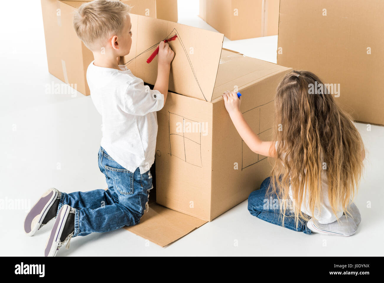 Cute little boy and girl drawing house on cardboard box - Stock Image