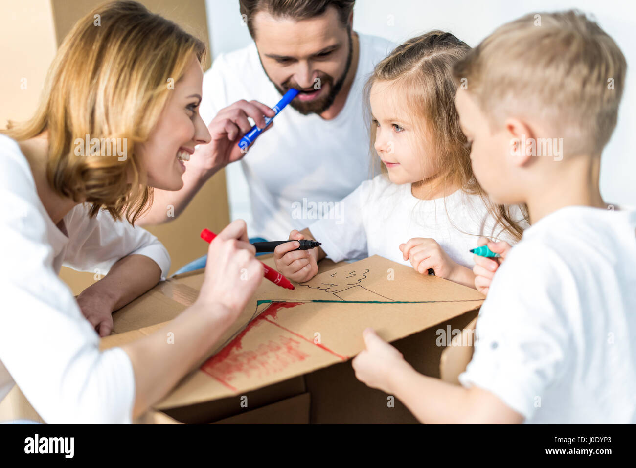 Happy young family of four drawing on cardboard box together - Stock Image