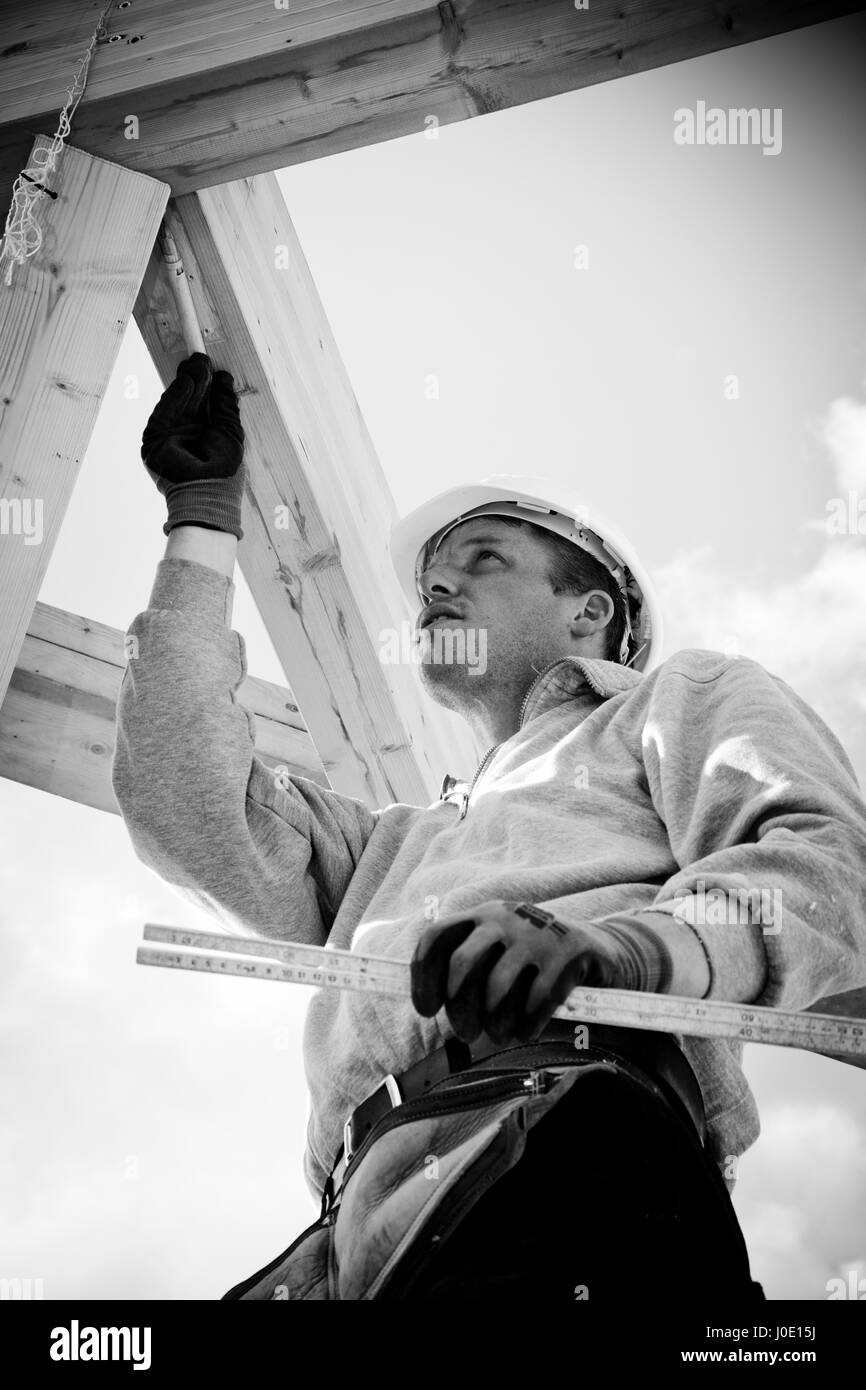 carpenter with tools working on timber construction Stock Photo