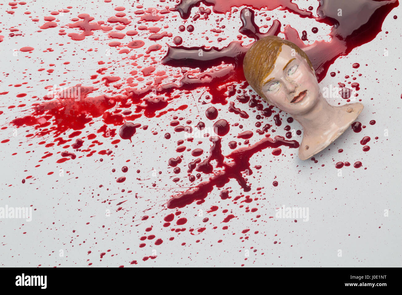 Adult woman doll head on blood spattered white background - Abstract concept  of violence against a woman - Stock Image