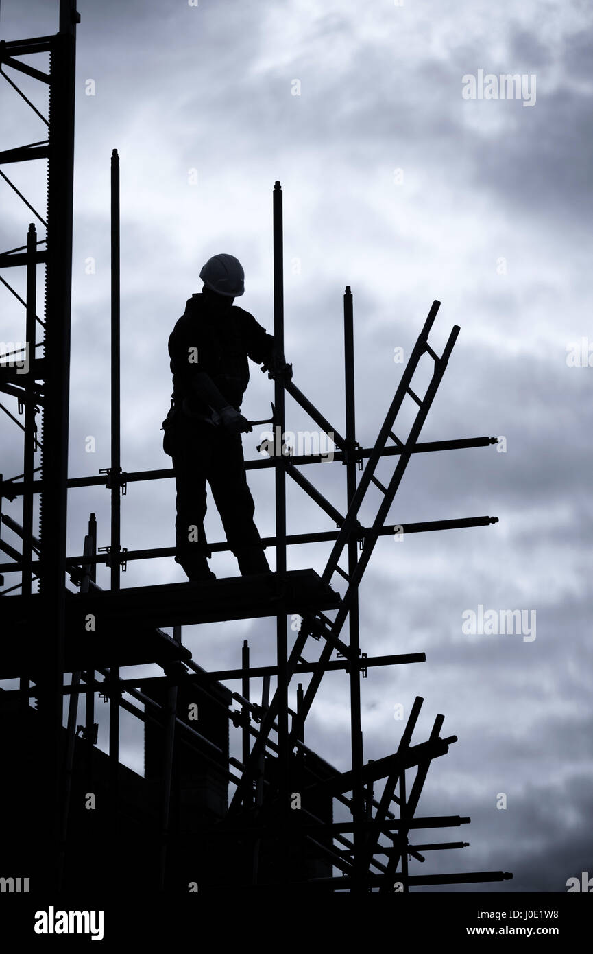silhouette of construction worker on scaffolding, Blue toned - Stock Image