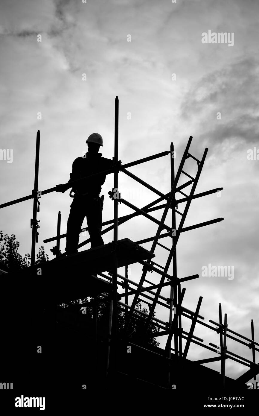 silhouette of construction worker on scaffold - Stock Image