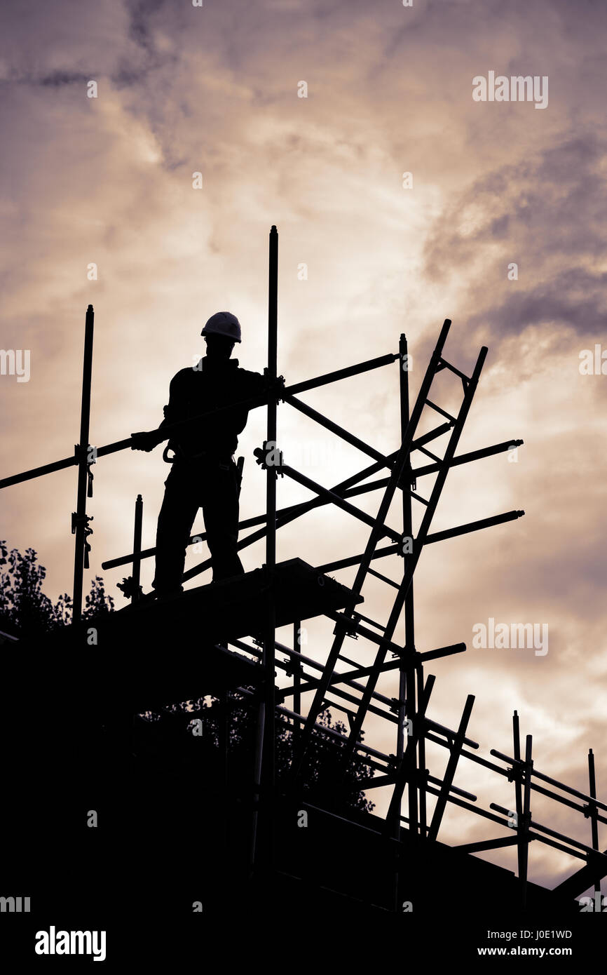 silhouette of construction worker with ladder on scaffolding. Purple toned - Stock Image