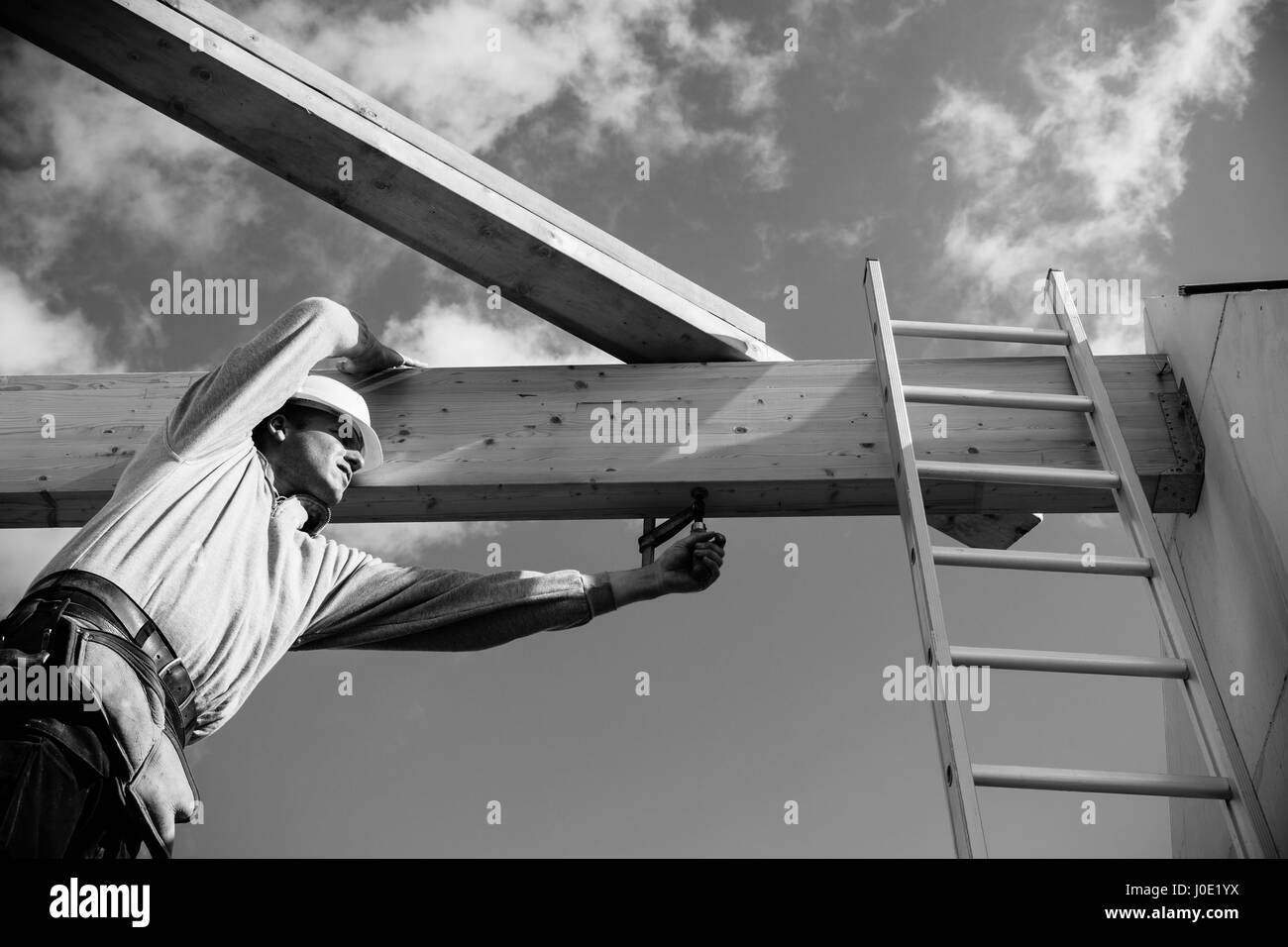 carpenter at work with wooden  roof construction.Monochrome - Stock Image