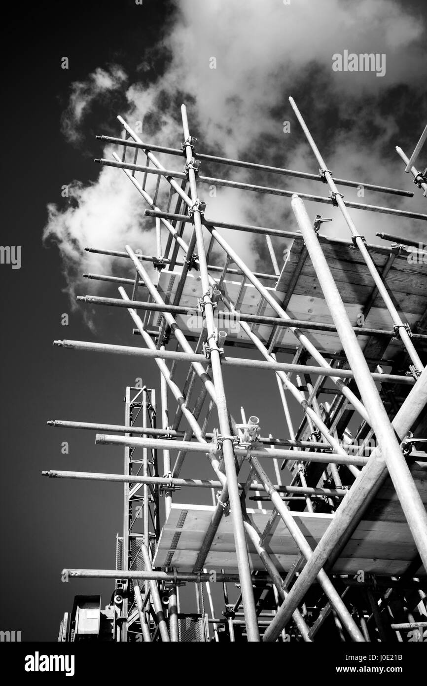 scaffolding construction with ladder against sky - Stock Image