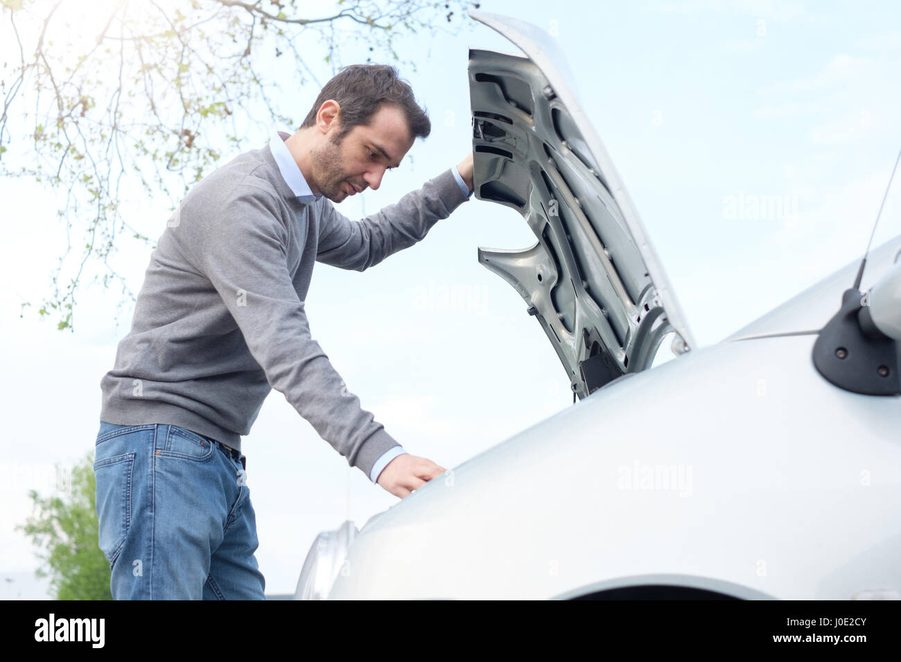 Stressed man checking engine after vehicle breakdown - Stock Image