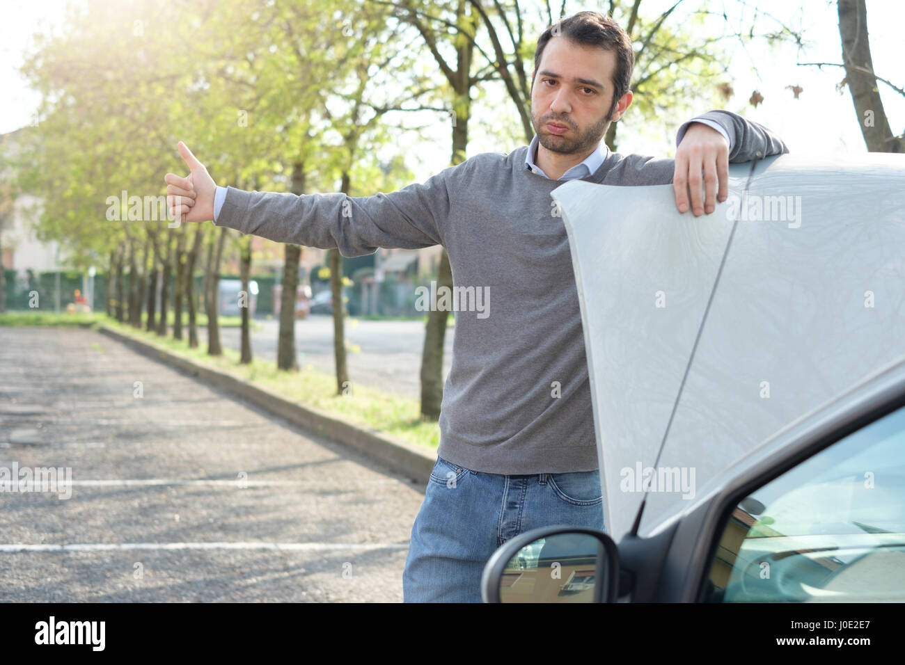 Man hitchhiking on the road after a vehicle breakdown - Stock Image
