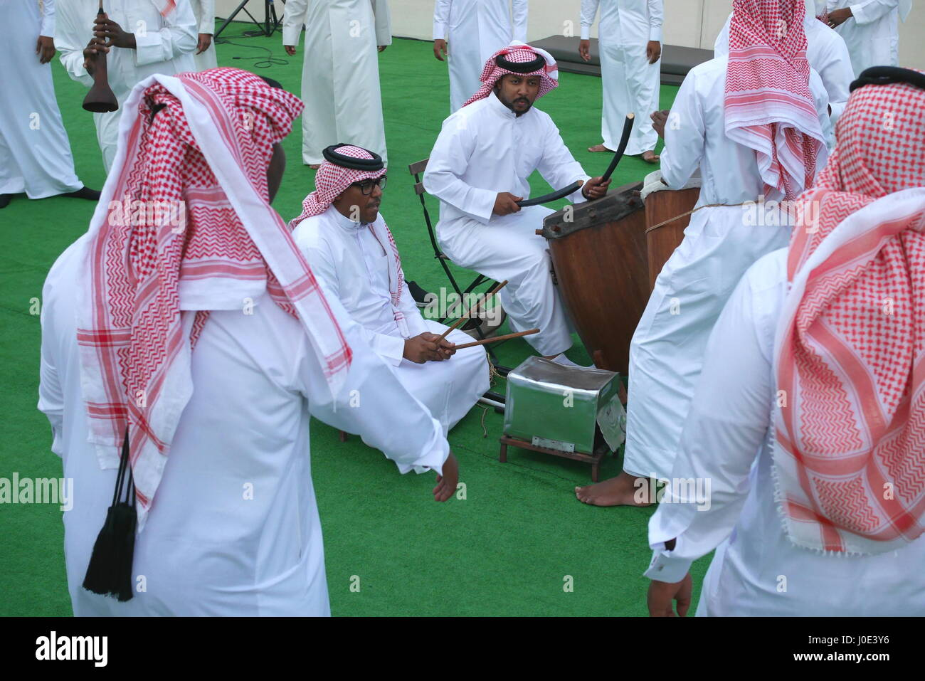 Traditional Bahrain dance accompanied by drums and mizmar. The men are wearing dishdashas, ghutra (keffiyeh) and - Stock Image