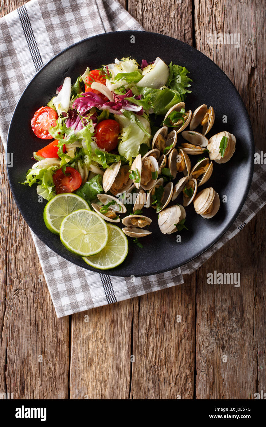 Fresh clams with lime and greens and mix salad close-up on a plate. Vertical view from above - Stock Image
