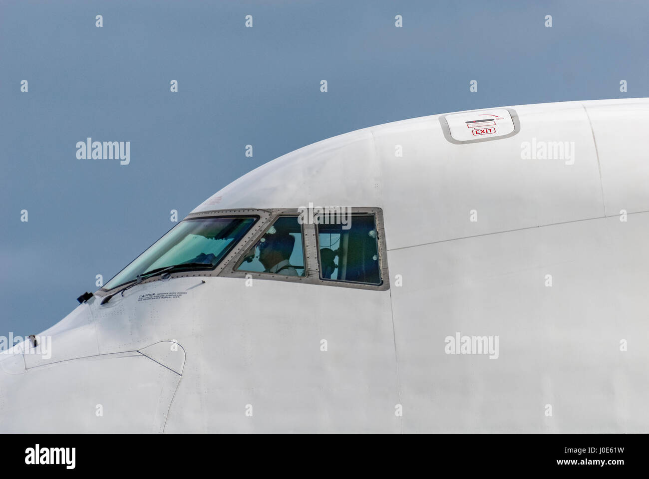 Jumbo jet Boeing 747 cockpit with pilots visible. Close uo. - Stock Image