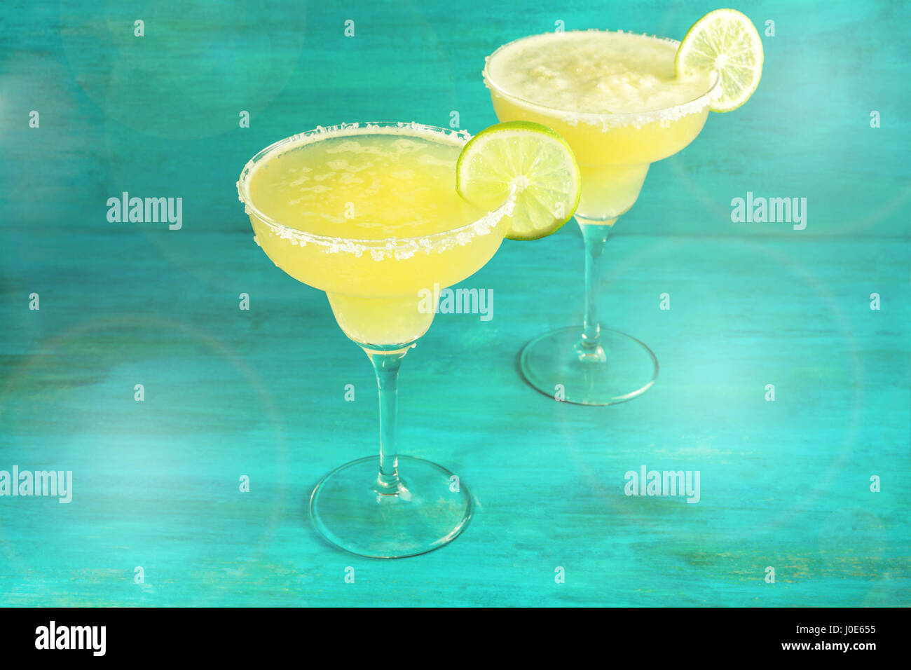 Lemon Margarita cocktails on vibrant teal with copyspace - Stock Image