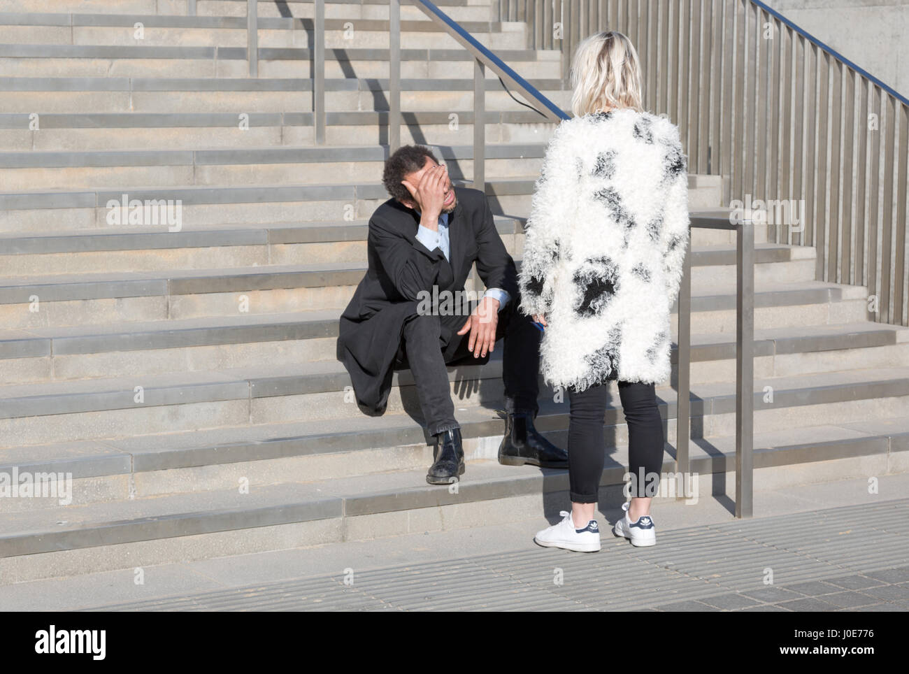 White adult woman standing next to sitting in stairs man and arguing. Horizontal full frame - Stock Image