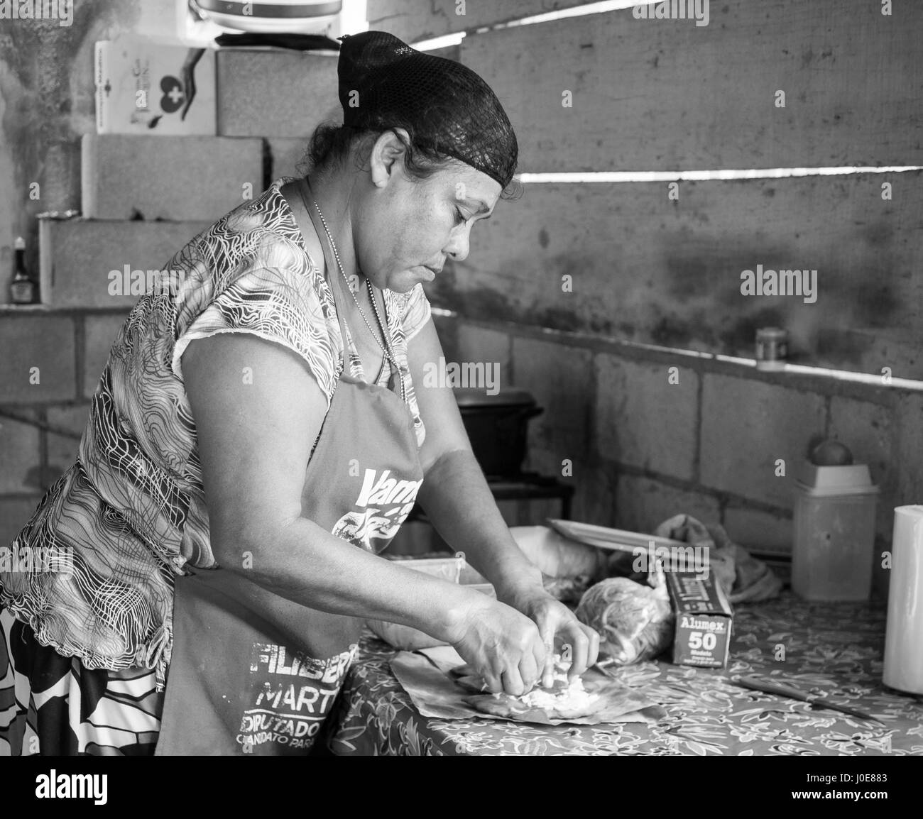 Lunch Preparation monochrome. A woman prepares a street lunch by filling a tortilla with salad and chicken in a - Stock Image