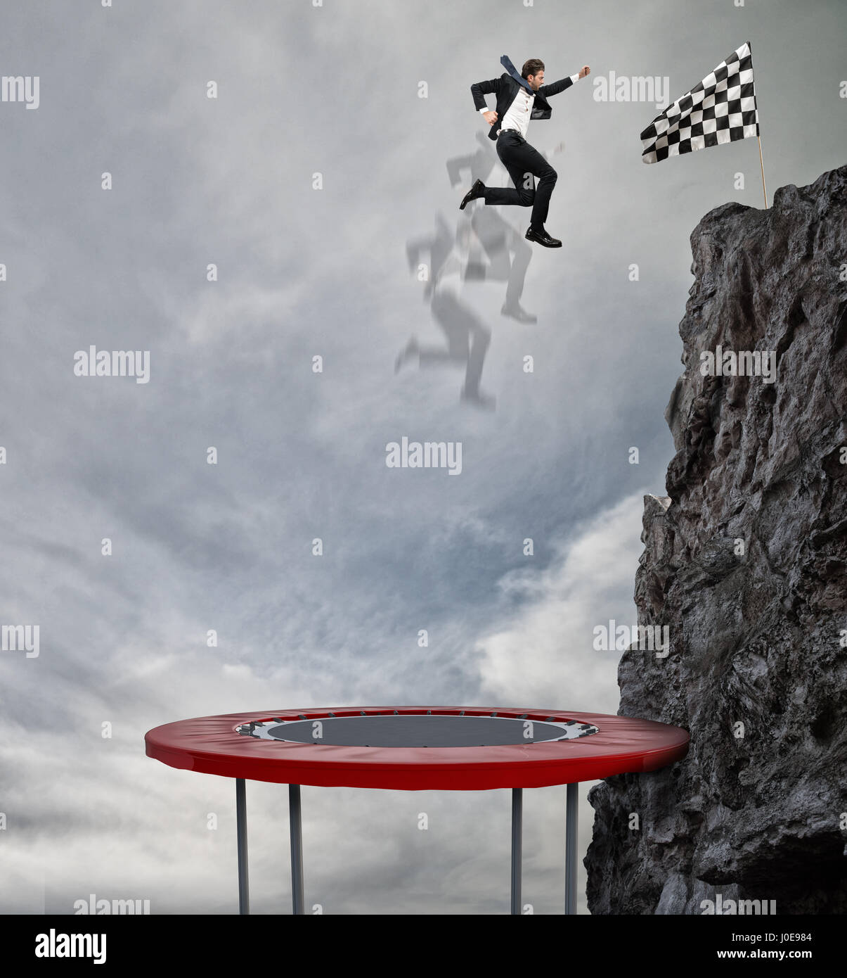 Businessman jumping on a trampoline to reach the flag. Achievement business goal and Difficult career concept - Stock Image