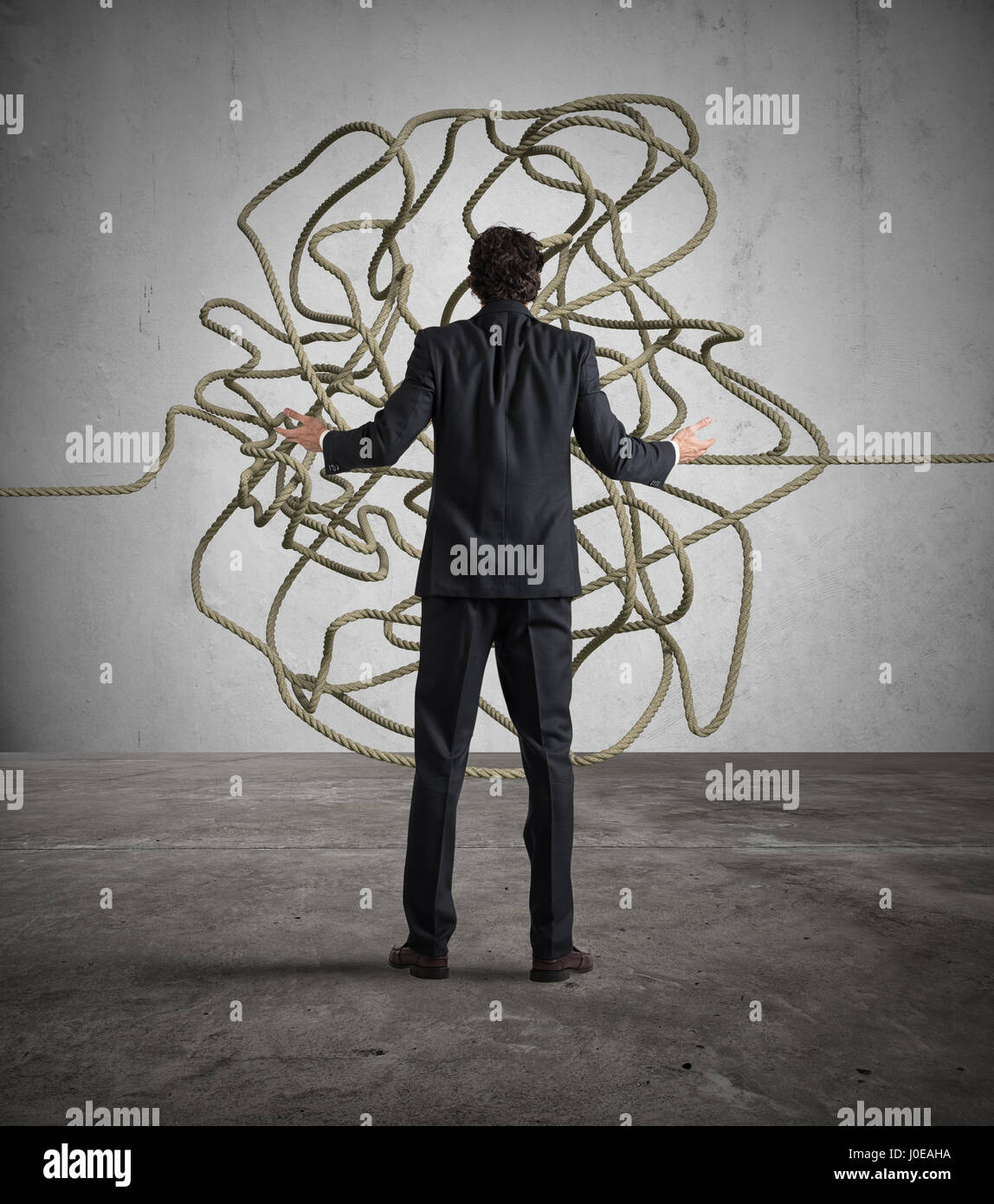 Businessman resolves the tangle - Stock Image
