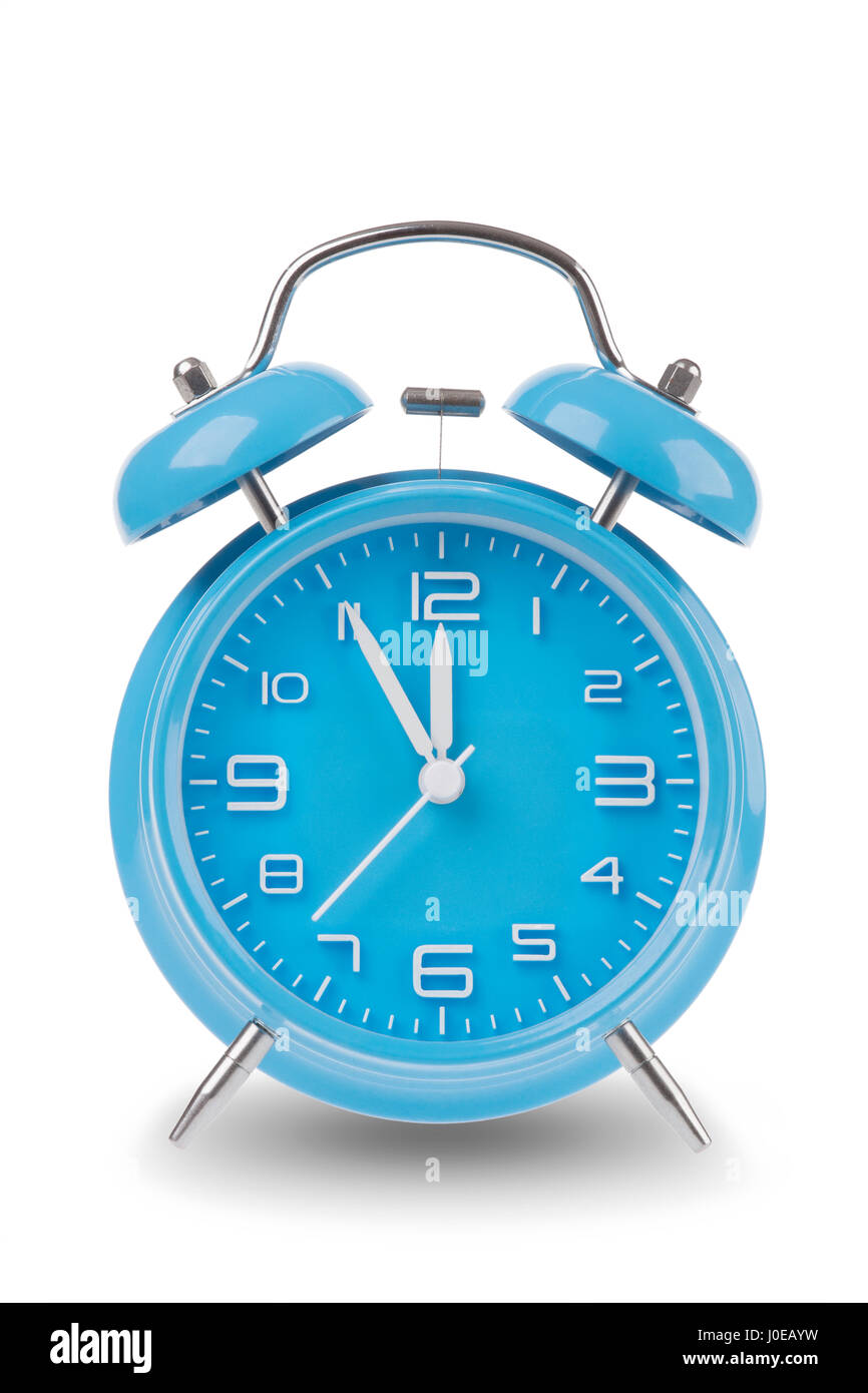 Blue alarm clock with the hands at 5 minutes till 12 illustrating time is running out isolated on a white background - Stock Image