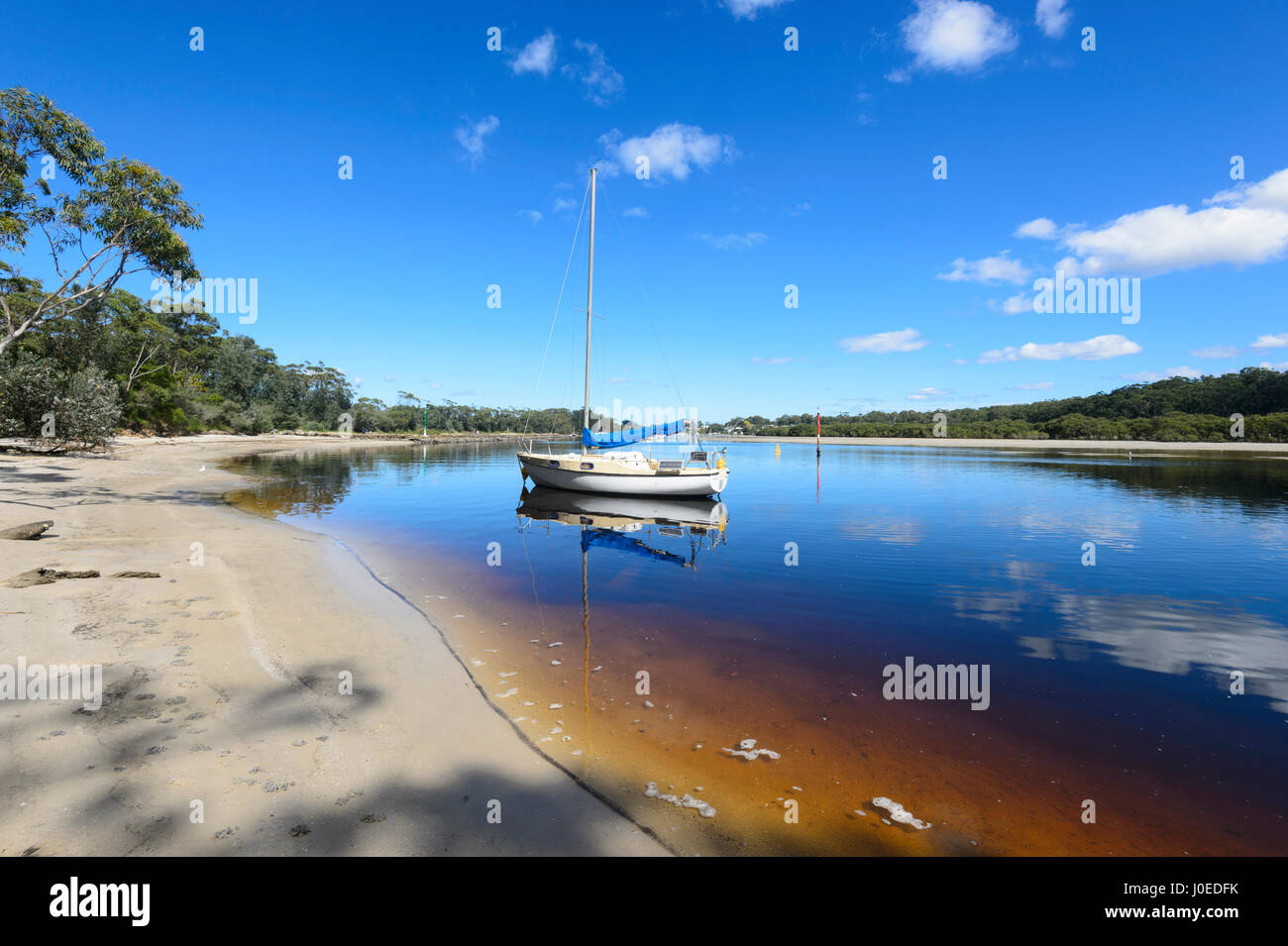Sailing Boat moored in tannin-stained Currambene Creek, Huskisson, South Coast, New South Wales, NSW, Australia - Stock Image