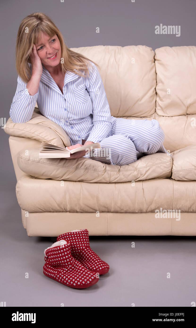 Woman  wearing pyjamas sitting on a sofa reading a book - Stock Image