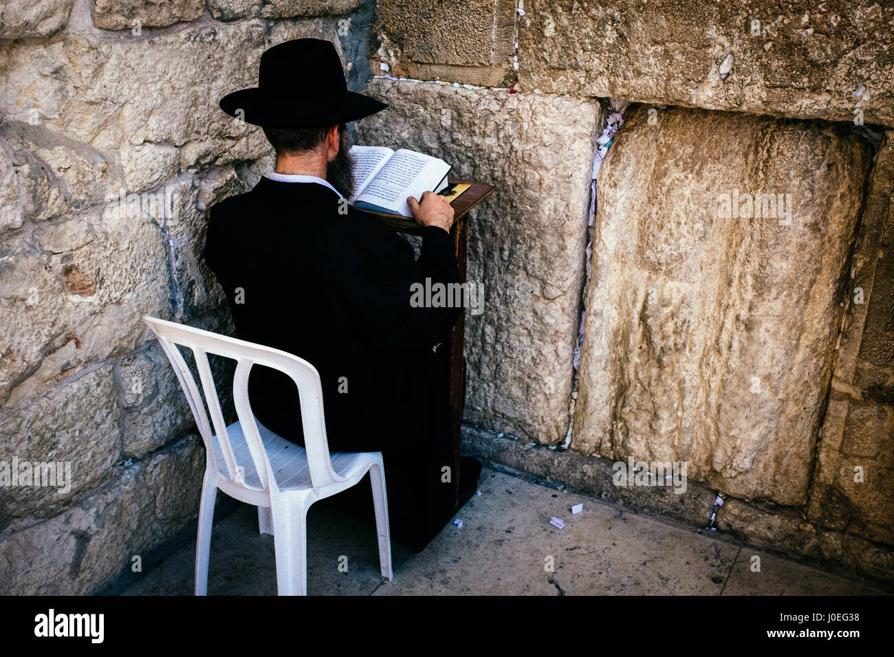 An orthodox Jews sits in the corner up against the Wailing Wall saying prayers from a Siddur praying book. - Stock Image