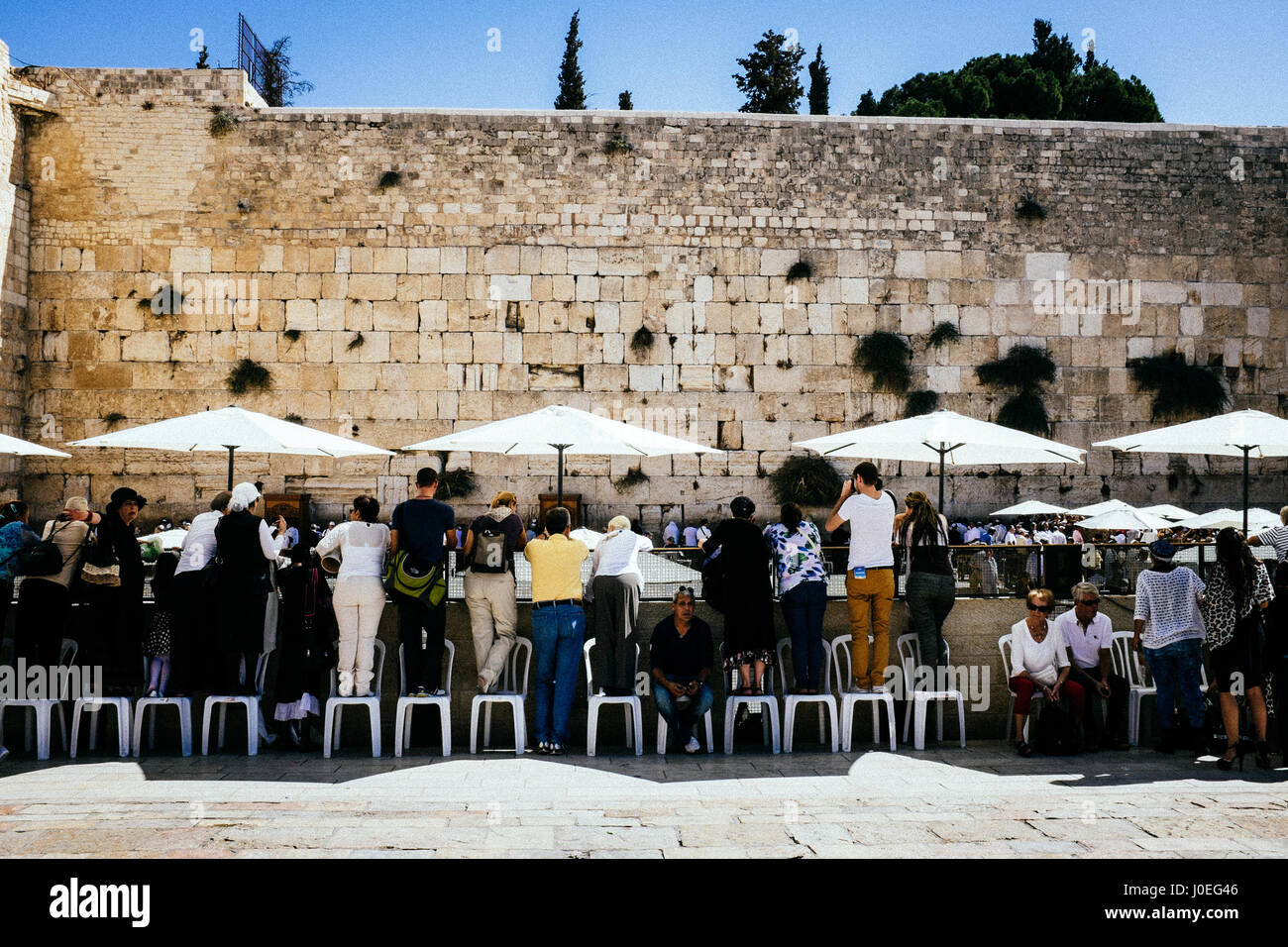 Woman and tourist blend together and take pictured of the holy Wailing Wall and the praying Jews in front of it. - Stock Image