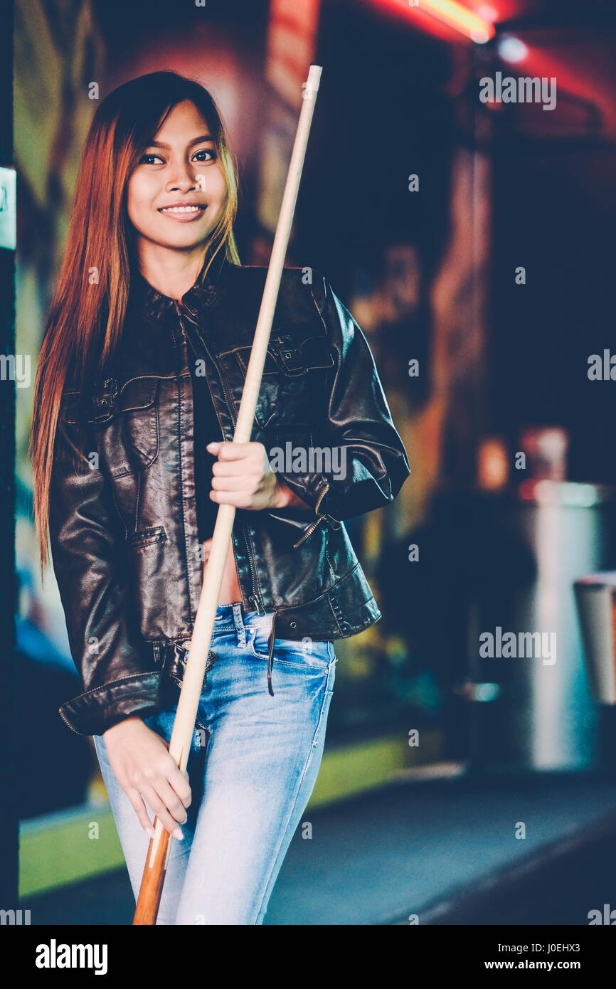 Young beautiful girl wearing leather jacket in a billiard club, with cue stick preparing for the game - Stock Image
