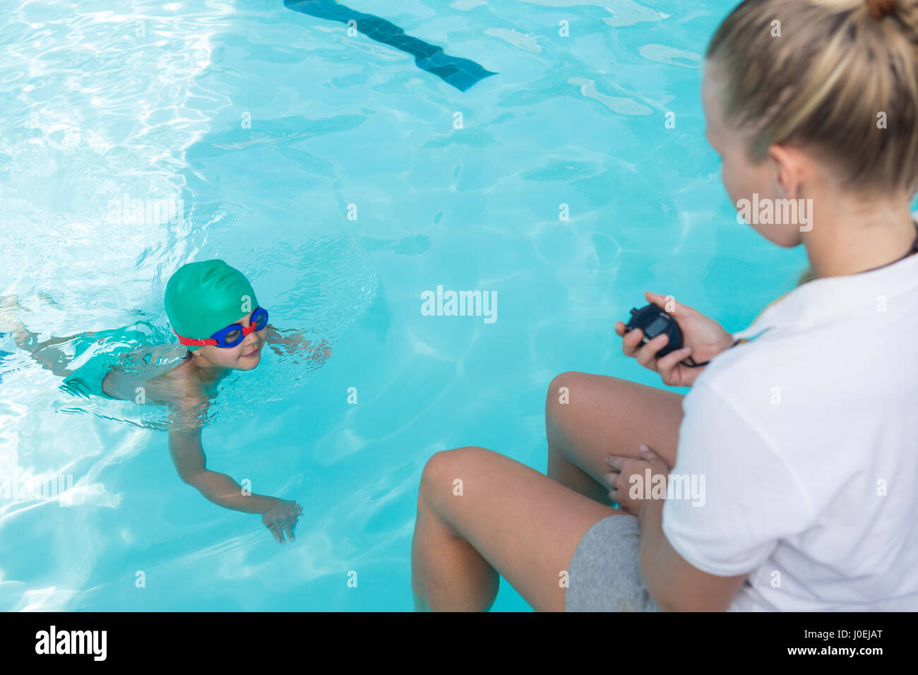 Female trainer monitoring time of boy swimming in pool at the leisure center - Stock Image
