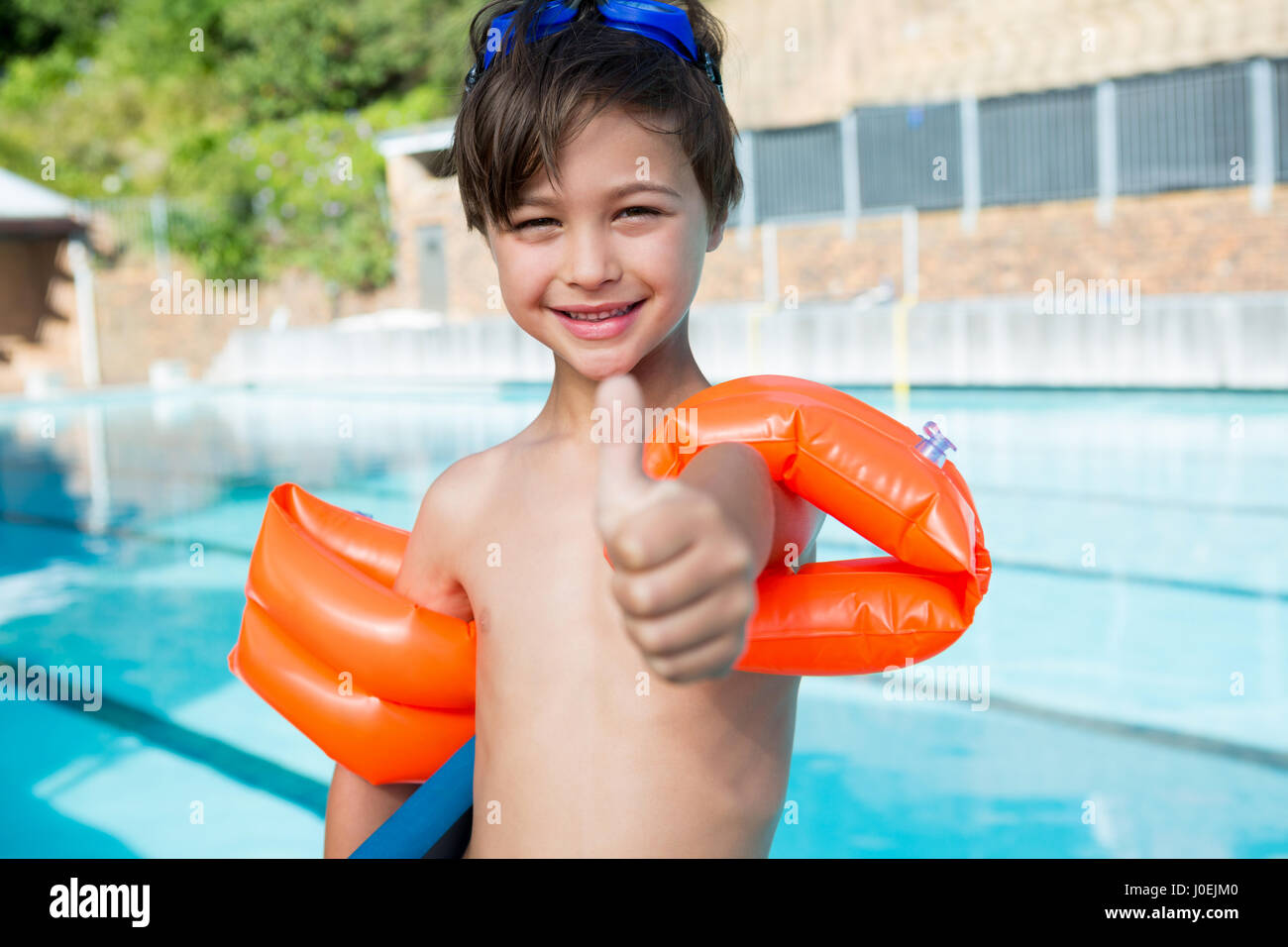 Young boy showing thumbs up at poolside in leisure center Stock Photo